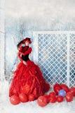 Den trendiga kvinnan i rött slösar att posera för klänning Arkivbild
