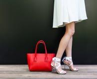 Den trendiga kvinnan med långa härliga ben i bandbandet Stilleto skor anseende på den svarta bakgrunden Flickaställningar Royaltyfria Bilder