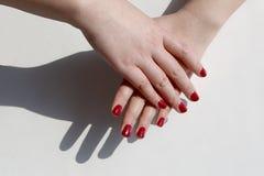 Den trendiga kvinnans hand målade rött spikar polermedel, superposition av en hand å andra sidan royaltyfri fotografi