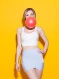 Den trendiga moderna flickan som poserar i färgrik överkant och kjol, blåser upp den röda bubblan från tuggummi på gul bakgrund i Arkivbilder