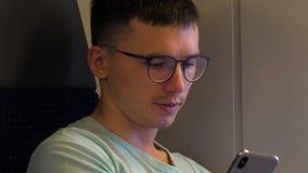 Den trendiga unga grabben bär stilfullt exponeringsglasbruk hans telefon arkivfilmer