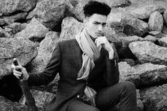den trendiga unga mannen som sitter p?, vaggar n?ra havet fotografering för bildbyråer