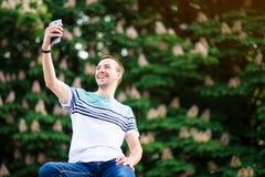 Den trendiga unga paris mannen som tar en selfie med smart telefondet fria parkerar in, på solig sommardag arkivfoto