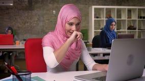 Den trevliga arabiska kvinnan är att gäspa som är avkopplat och att ta pauser från att arbeta på bärbara datorn som bakom sitter  lager videofilmer