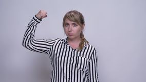 Den trevliga caucasian för showmakt för den unga kvinnan gesten med förtroende och kopplad av stillhet vänder mot inomhus stock video