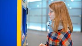 Den trevliga damen köper en biljett i varuautomaten som betalar vid kreditkorten Paypass arkivfilmer