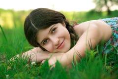 Den trevliga flickan med härligt leende poserar på gren Fotografering för Bildbyråer