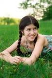 Den trevliga flickan med härligt leende poserar på gren Royaltyfri Bild