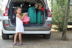 Den trevliga fundersamma lilla flickan med den vita klänningen laddar bilen Royaltyfri Foto