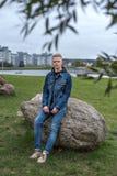Den trevliga grabben i jeansomslag sitter på en sten i parkera i en skymning Royaltyfria Bilder