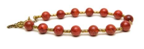 Den trevliga halsbandet med röda pärlor på vit bakgrund Arkivbild