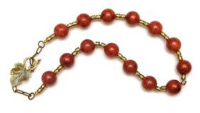 Den trevliga halsbandet med röda pärlor på vit bakgrund Arkivbilder