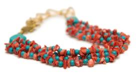 Den trevliga halsbandet med röda pärlor på vit bakgrund Arkivfoto