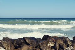 Den trevliga havssikten med vågor med skum och vaggar middagar på havskusten av Blacket Sea arkivfoton