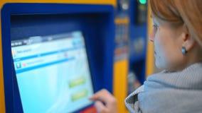 Den trevliga kvinnan köper en biljett i varuautomaten som betalar vid kreditkorten Paypass arkivfilmer