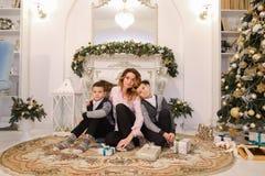 Den trevliga kvinnan och modern och barn med pojkar ser och ler på c Royaltyfria Bilder