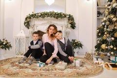Den trevliga kvinnan och modern och barn med pojkar ser och ler på c Royaltyfri Bild