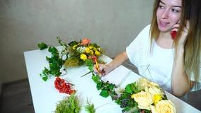 Den trevliga kvinnliga blommaformgivaren accepterar beställning för blommaordningen på telefonen som sitter på tabellen i ljust k stock video