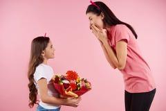 Den trevliga lilla dottern ger blommor till härligt fotografering för bildbyråer