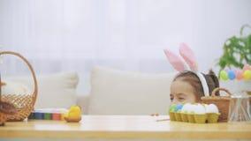 Den trevliga lilla flickan med kaninöron döljer under tabellen mycket av påskgarneringar Den lilla gulliga vita kaninen är lager videofilmer