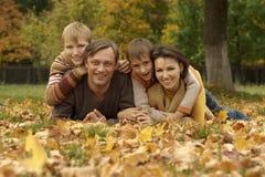 Den gulliga familjen som ligger i höst, parkerar arkivbild