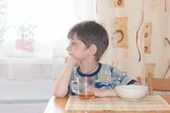den trevliga pojkefrukosten sitter tabellen Arkivfoto