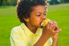 Den trevliga pojken har en frukost Arkivfoton