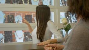 Den trevliga säljarekonsulenten erbjuder att välja några smycken till en kund i ett smyckenlager Arkivbild