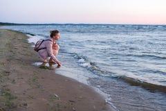 Den trevliga tonåringflickan går nära havet på kusten på th royaltyfria foton