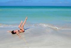 Den trevliga ung flicka har gyckel i stranden Arkivfoton