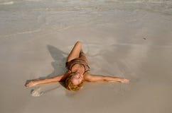 Den trevliga ung flicka har gyckel i stranden Fotografering för Bildbyråer