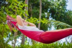 Den trevliga unga damen lyssnar musik i mindre kulle under plamträd på trop Fotografering för Bildbyråer