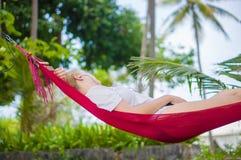 Den trevliga unga damen lyssnar musik i mindre kulle under plamträd på trop Royaltyfria Bilder