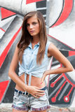 Den trevliga unga kvinnan i jeans passar nära tegelstenväggen Royaltyfri Fotografi