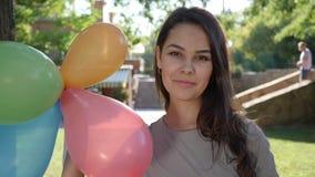 Den trevliga unga kvinnan med hänglsen på tänderna ler, och hållballonger i hand på bakgrund gör grön träd arkivfilmer