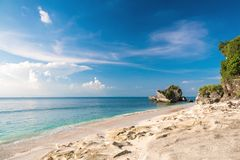 Den tropiska sandstranden med vaggar och det blåa havet i Padang Padang Royaltyfri Fotografi