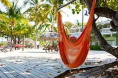 Den tropiska semesterorten med chaisen longs och hängmattor Arkivbilder