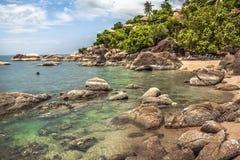 Den tropiska stranden med kullen och palmträd i lagun med genomskinlig turkos bevattnar och rundar det närliggande tropiska hotel Arkivbilder