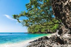 Den tropiska stranden och svart vaggar med havet i Bali blå lagun Royaltyfria Foton
