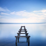 Den träpir eller bryggan återstår på en blå sjö. Lång exponering. Arkivbild