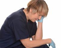 Den trött sjuksköterskan med huvudet räcker in Arkivbild