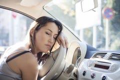 Den trötta kvinnan sovande på styrning rullar in hennes bil Fotografering för Bildbyråer