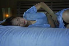 Den tryckta ned härliga asiatiska kinesiska flickan som lider menstruation, och perioden smärtar känsla som är sjuk i säng på nat royaltyfria foton