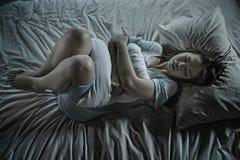 Den tryckta ned härliga asiatiska kinesiska flickan som lider menstruation, och perioden smärtar känsla som är sjuk i säng på nat arkivbilder