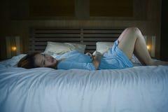 Den tryckta ned härliga asiatiska koreanska flickan som lider menstruation, och perioden smärtar känsla som är sjuk i säng på nat arkivfoto