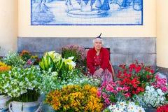 Den Ttraditional kvinnan säljer blommor på en marknad av Funchal, Portugal Royaltyfri Bild