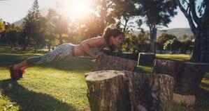 Den tuffa unga kvinnan som gör liggande armhävningar på en journal på, parkerar Royaltyfria Bilder