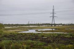 Den tunga grå färgen fördunklar i den kalla hösthimlen över gröna fält, träd, skogar, strömmar För storm elektriska poler Fotografering för Bildbyråer