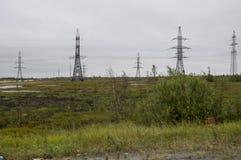 Den tunga grå färgen fördunklar i den kalla hösthimlen över gröna fält, träd, skogar, strömmar För storm elektriska poler Arkivbild