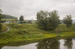 Den tunga grå färgen fördunklar i den kalla hösthimlen över by med små hus som är långväga i bergen och fälten Små flodflöden arkivfoto